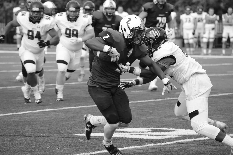 Sophomore Kyle Hill stiff arms Bentley defender.