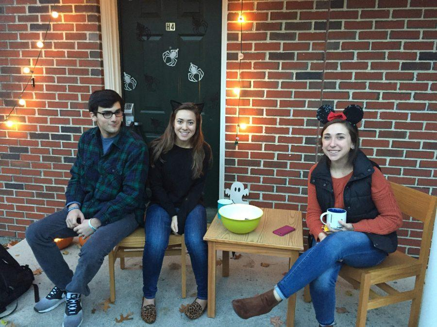 Seniors Micaela Barry, Gabrielle Aveni hand out candy to trick-or-treaters at Father  Bernard Court with underclassman Andrew Bompastore.