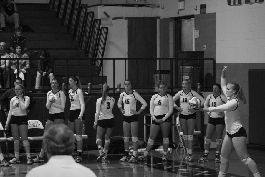 Volleyball+players+on+the+sideline+look+on+as+teammate+Katy+Teets+is+about+serve+to+SNHU+on+Oct.+4.