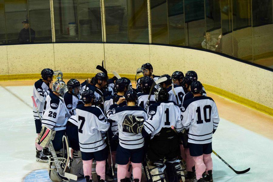 Saint Anselm Hawks huddle together as a team.