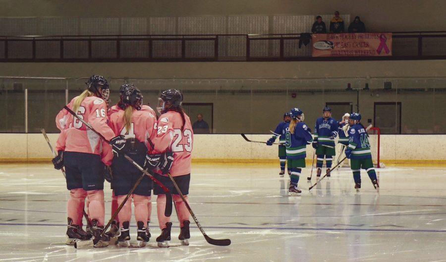 Maura Kieft, Sara McNamara, and Martha Findley (left to right) huddle on ice.