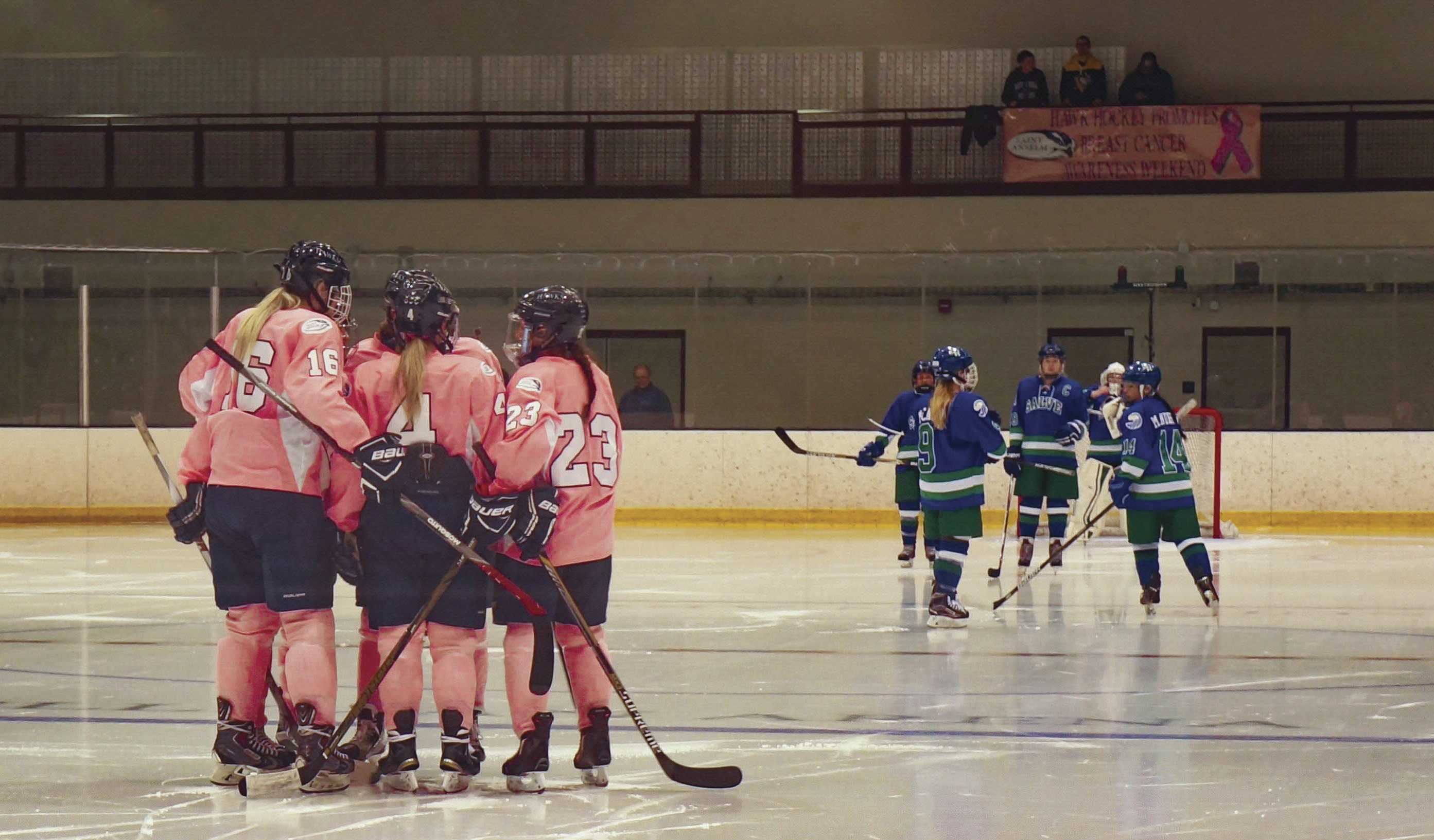 Maura Kieft, Sara McNamara, and Martha Findley (left to right) huddle on ice.