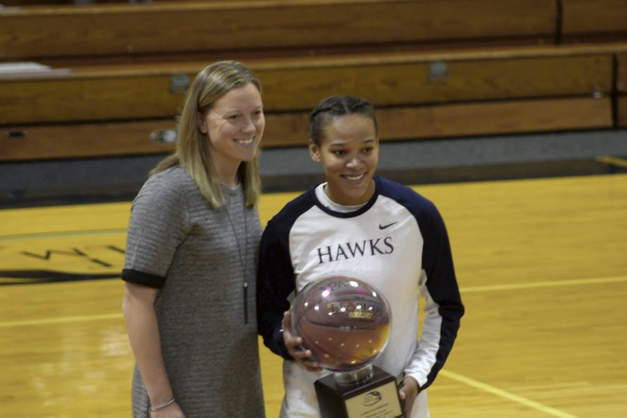 Senior Candace Andrews receives award for 1000 points from head coach Julie Plant.