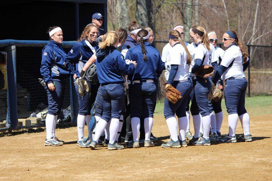 Hawks softball huddling together on the field.