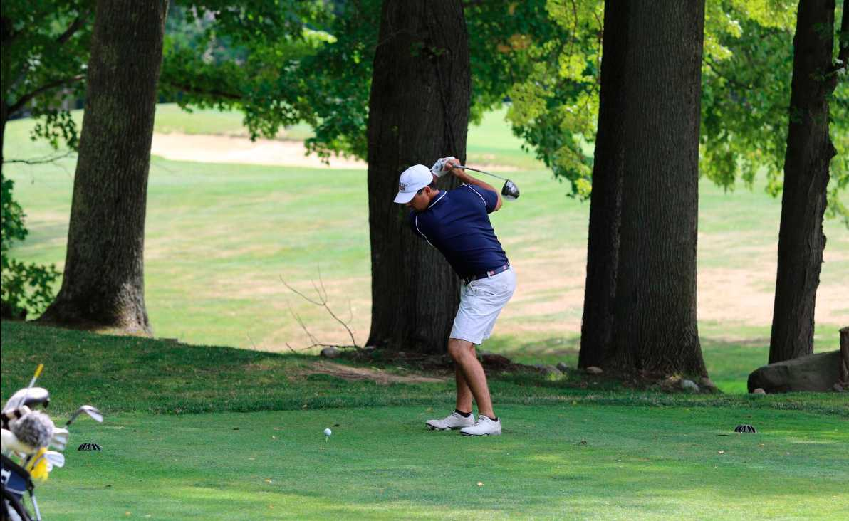 Senior Nick Markham keeps his eye on the ball as he aims for the fairway.