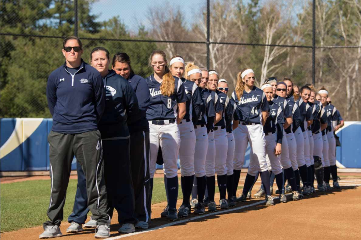 Softball team and staff stand during the national anthem before their game.