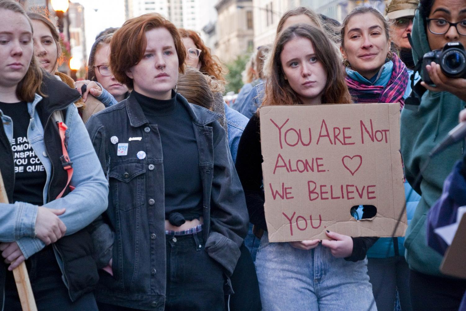 "A group of young women stand in protest in Chicago, Illinois, in support of Dr. Christine Blasey Ford, saying, ""You are not alone. We believe you."""