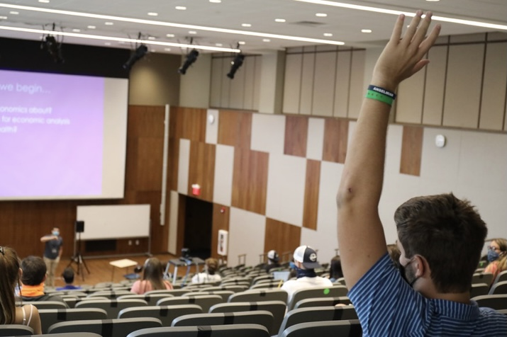 A student raises his hand in a socially-distanced lecture in the new Melucci theater.