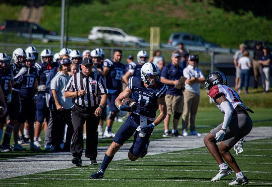 Senior+receiver+Bobby+Long%2C+%2317%2C+runs+down+the+sideline+in+Hawks+homecoming+game+against+Franklin+Pierce